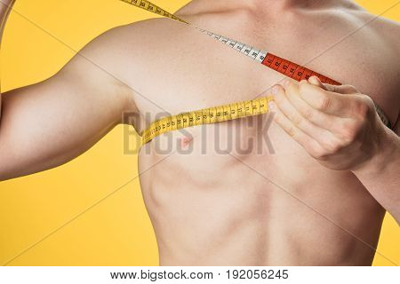 The athlete measures his body with a measuring tape, the athlete on a yellow background