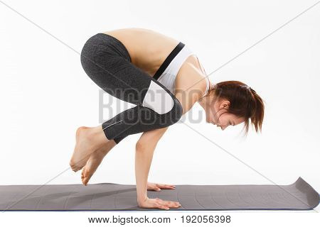 Young woman exercise yoga supported headstand over white
