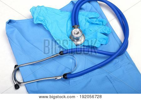 Medical stethoscope and gloves lying on blue uniform doctor close up. The store of medical instruments and instruments, the therapist's work space, the physical concept of measuring blood pressure.