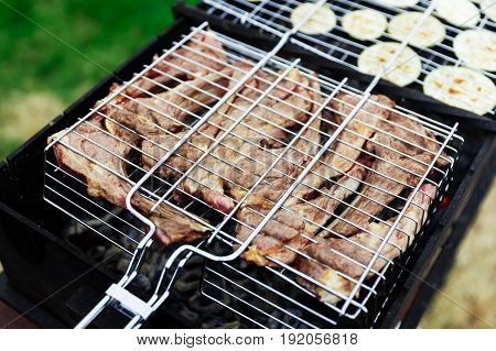 Barbecue meat with bone and fresh vegetables on grill in summer against green lawn background