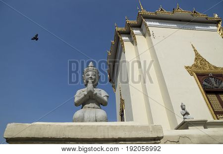 Buddha statue bird and temple at palace in Phnom Penh Cambodia