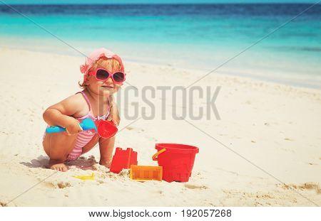cute little girl play with sand on tropical beach