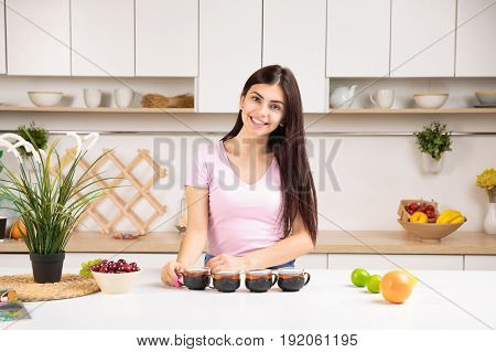 Attractive woman offering tea on the kitchen