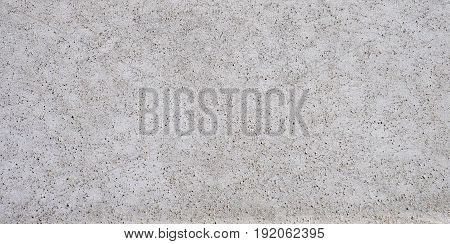 Cement mixed small gravel stone wall. Abstract concrete gray background. Concrete seamless texture. gravel oval elements seamless pattern