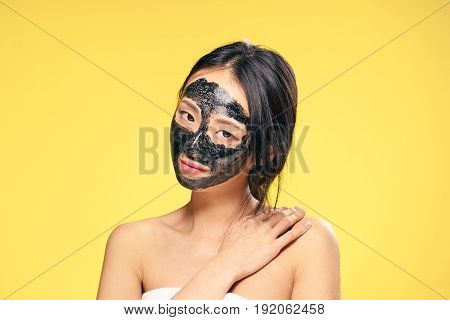 Facial skin care, skin problem, cleansing mask, woman in cosmetic mask, woman on yellow background.