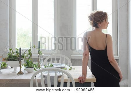 Back view of woman leaning on served table in dining room.