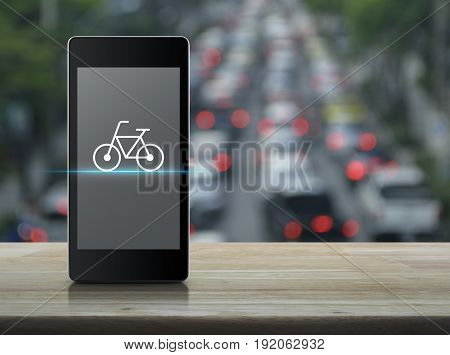 Bicycle flat icon on modern smart phone screen on wooden table over blur of rush hour with cars and road Bike shop online concept
