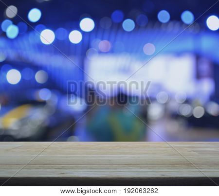 Empty wooden table over defocused light and shadow of shopping mall