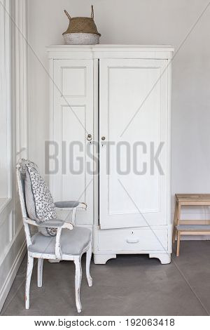 Vertical indoors shot of white aged closet and chair.