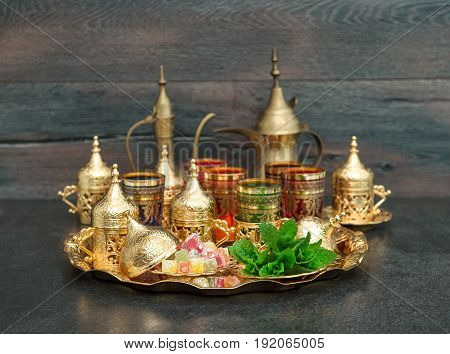 Oriental tea coffee table golden dishes with delight and mint. Ramadan kareem. Eid Mubarak