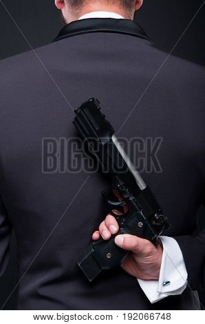 Criminal Gangster Holding Revolver On His Back