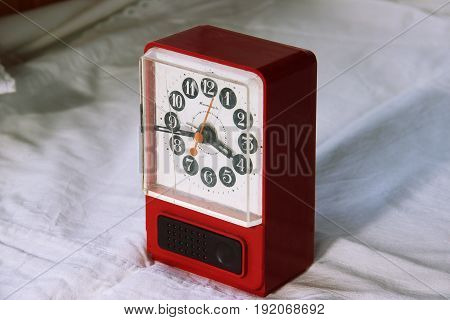 Red alarm clock in bedroom. Without fifteen four in the early morning.
