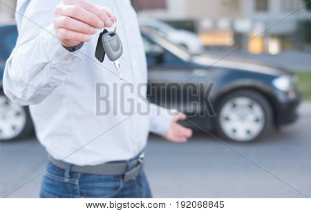Man Holding A Car Key Next To His Vehicle