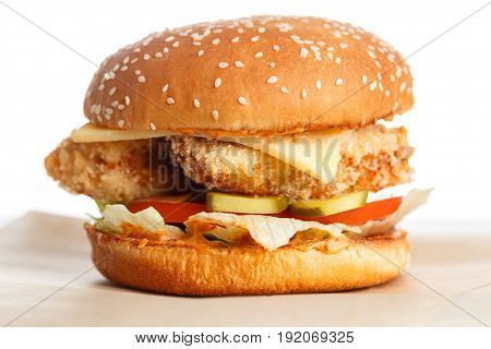 Big tasty chicken burger wooden table. bun with sesame seeds, vegetables, iceberg lettuce, pickled cucumber