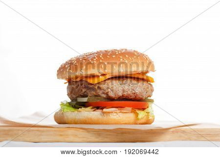 Big tasty burger with meat Patty wooden table.. bun with sesame seeds, vegetables, iceberg lettuce, pickled cucumber
