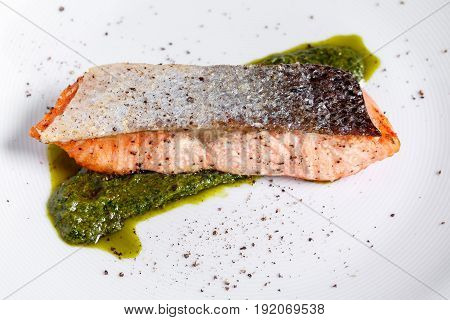 Salmon steak fillet - selective focus point. Green sauce of spinach arugula. Pesto sauce. on a white plate, the dish is served in the restaurant