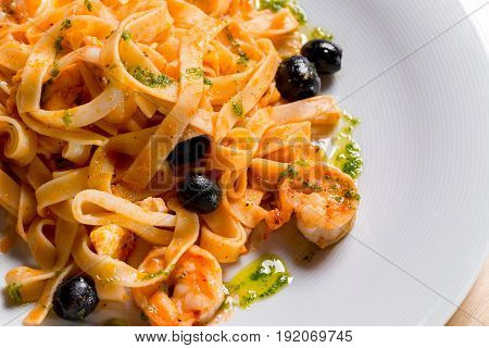 integral tagliatelle with shrimp and leek. On a white plate, the dish is served in the restaurant. Italian traditional food