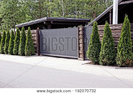Gray brown gate and a fence with decorative green trees in front of the asphalt road
