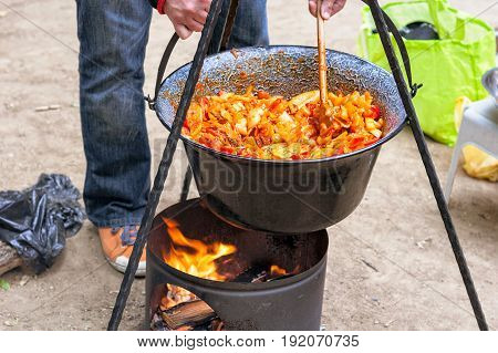 Making hungarian ratatouille in a cauldron on a campfire