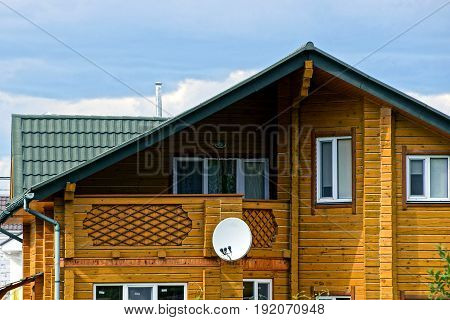 Facade of a brown wooden house with windows and satellite dish