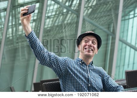 Very funny hipster fellow makes selfie by mobile phone
