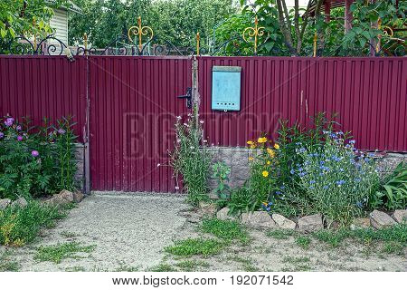 Red iron fence with mailbox with grass and flowers