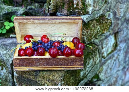 Ripe fruit in a wooden box on a brick wall