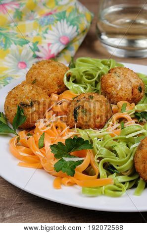 Spaghetti from carrots and spinach with chicken meatballs flavored cheese parmesan herb