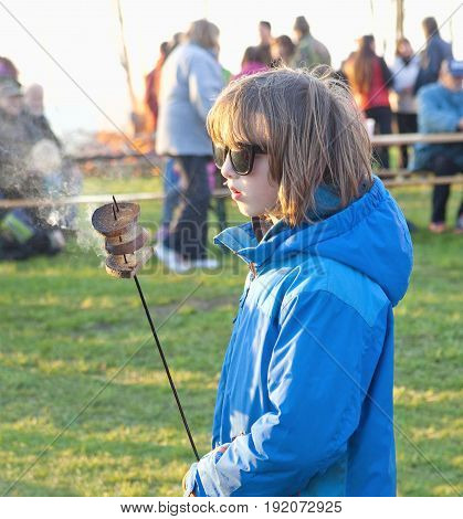 Boy with Blond Hair Grilling Toasts on Fire Outdoors