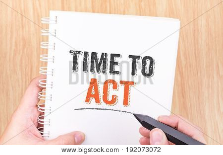 Time To Act Word On White Ring Binder Notebook With Hand Holding Pencil On Wood Table,business Conce