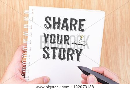 Share Your Story Word On White Ring Binder Notebook With Hand Holding Pencil On Wood Table,business