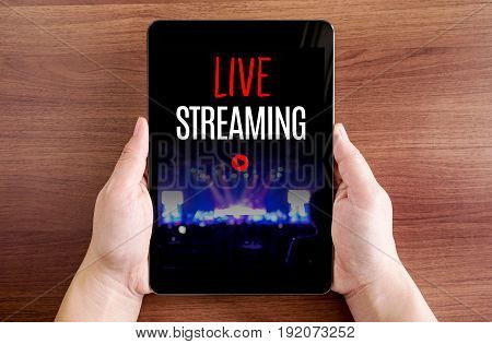 Two Hand Holding Tablet With Live Streaming And Play Icon On Screen At Dark Brown Table Top,digital