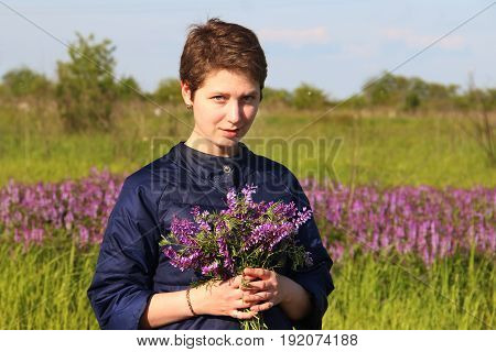 Portrait Of A Girl With Short Hair With A Bouquet Of Flowers.