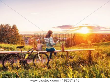 A girl is taking pictures of a dog on a smartphone beautiful sunset. Walking with a dog on a bike in the evening.