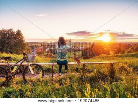 A young girl is taking pictures of a beautiful sunset on a smartphone. Walking with a dog on a bike in the evening.