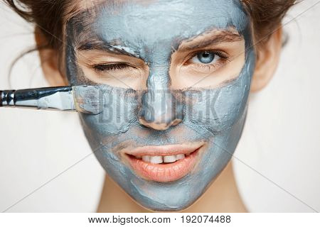 Close up photo of beautiful girl in hair curlers smiling winking looking at camera covering face with mack. Facial treatment. Beauty cosmetology and spa. Copy space.