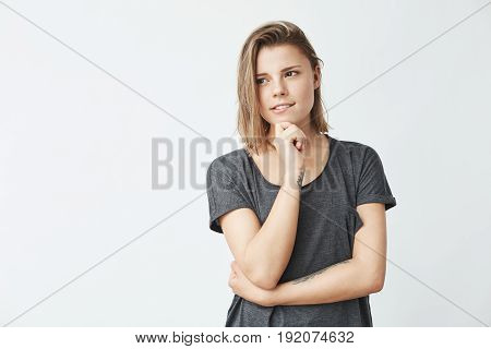 Dreamy young beautiful girl thinking with hand on chin looking in side over white background. Copy space.