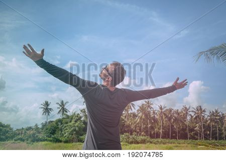 Man with arms wide open enjoying in nature.