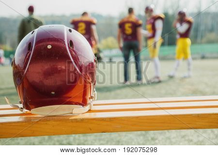 American football helmet on the bench and playing field.