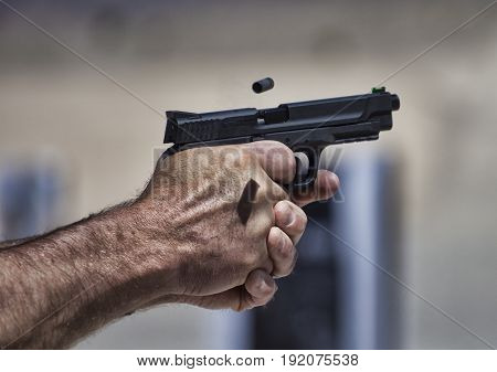 Brass flying from a handgun held tightly by the shooter