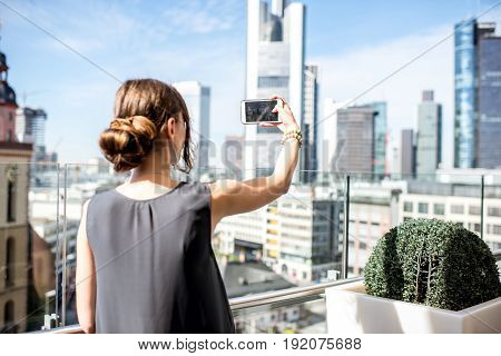 Young businesswoman photographing with phone skyscraper cityscape in Frankfurt