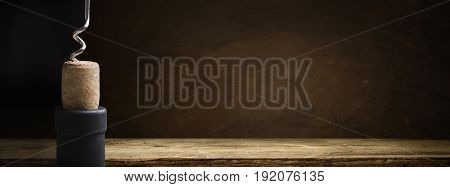 Bottle of wine with corkscrew on wooden background.