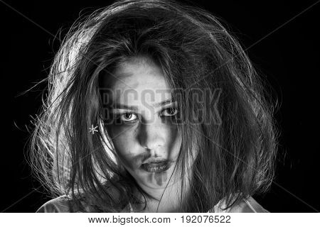pretty fun crazy girl with fluffy hair and smeared cosmetics on black background, monochrome