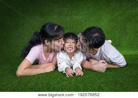 Happy Asian Chinese Parents And Daughters Lying On The Grass