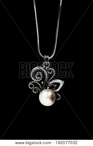 Elegant pearl pendant on silver chain isolated over black