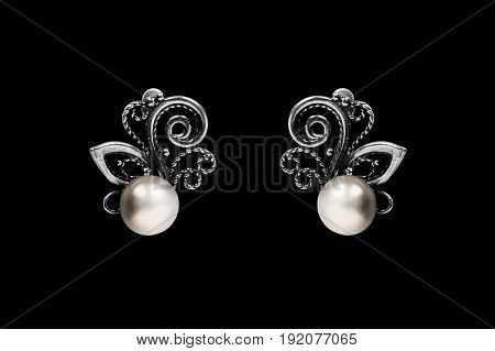 Vintage silver pearl earrings isolated over black