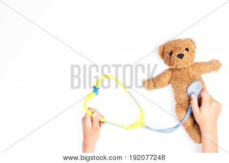 Kid hands with toy stethoscope and teddy bear on a white background. Top view. Copy space for text