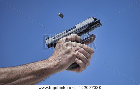Empty casing flying out of a semi automatic pistol