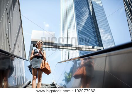 Young businesswoman with bag and phone getting down on the escalator during the business trip in the modern city