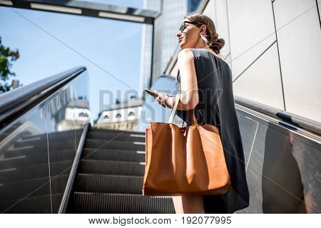 Young businesswoman with bag and phone getting up on the escalator during the business trip in the modern city